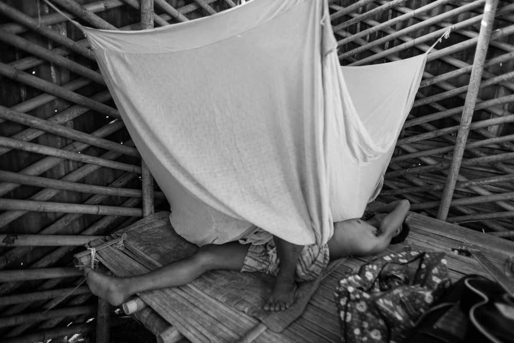 """Hkun Aung"", an unofficial name he has given, rolls around in pain under his mosquito net."