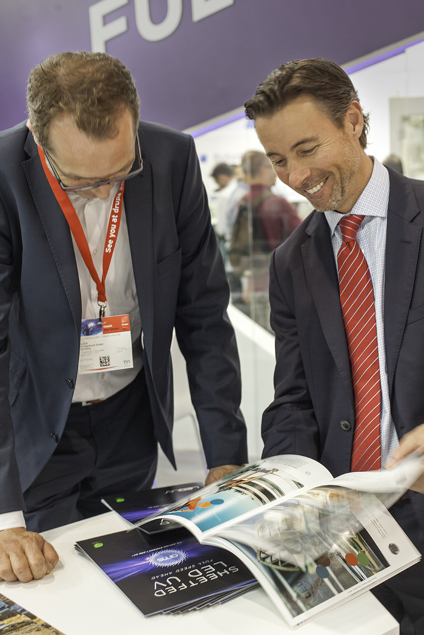 AMS president Steve Metcalf (right) flips through the LED Look Book at drupa 2016; this print piece shows off the ever-expanding capabilities of LED-based curing in sheetfed offset printing applications.