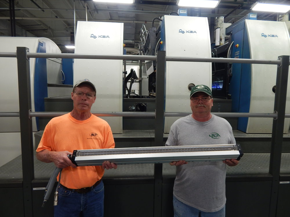 Press operators Keith Miller (left) and Pat Osier (right) show what the LED-UV curing module from AMS looks like when off the press. The module can last 20,000 hours, compared with 2,000 hours for a conventional UV lamp that uses mercury arc bulbs.