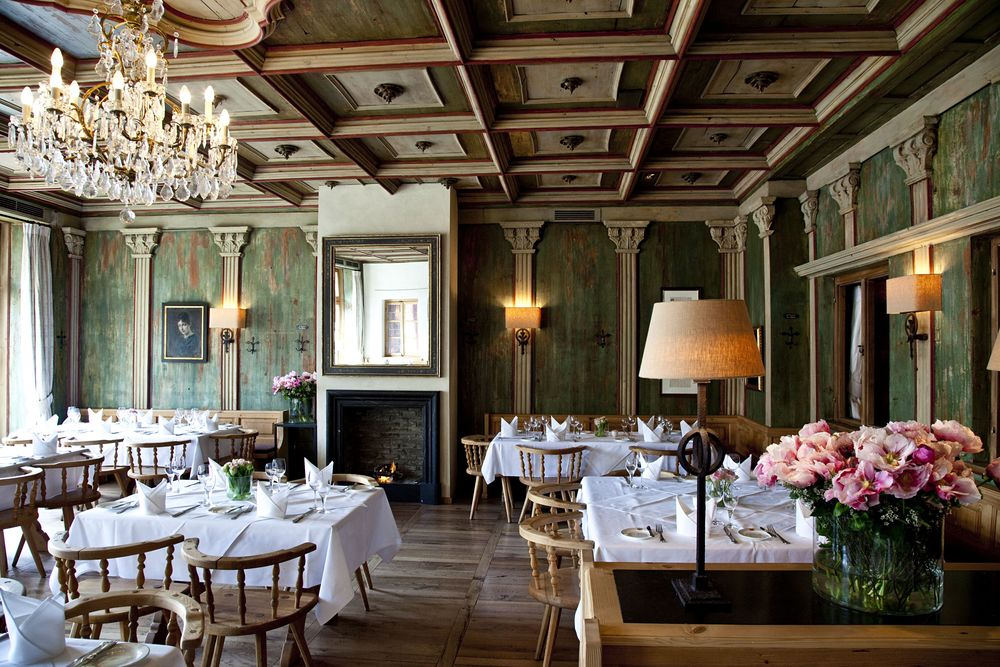 Dressed up with crisp, white table cloths, faux columns and painted  interior paneling, thoughtfully detailed coffered ceilings, fresh  flowers, and an inviting fire, the upstairs space is a touch more  elegant. Image via  restaurant website.
