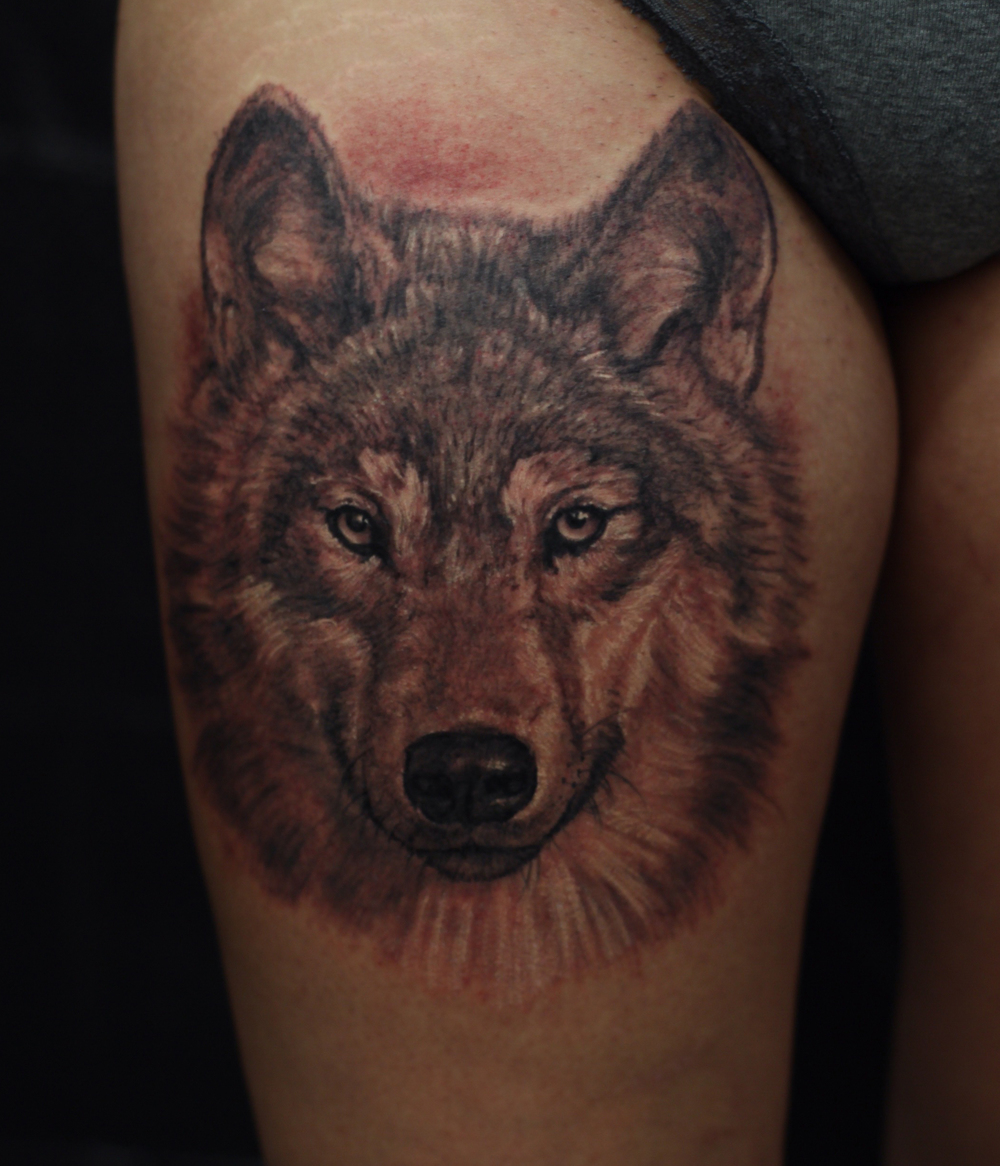 realistic wolf portrait tattoo on tigh