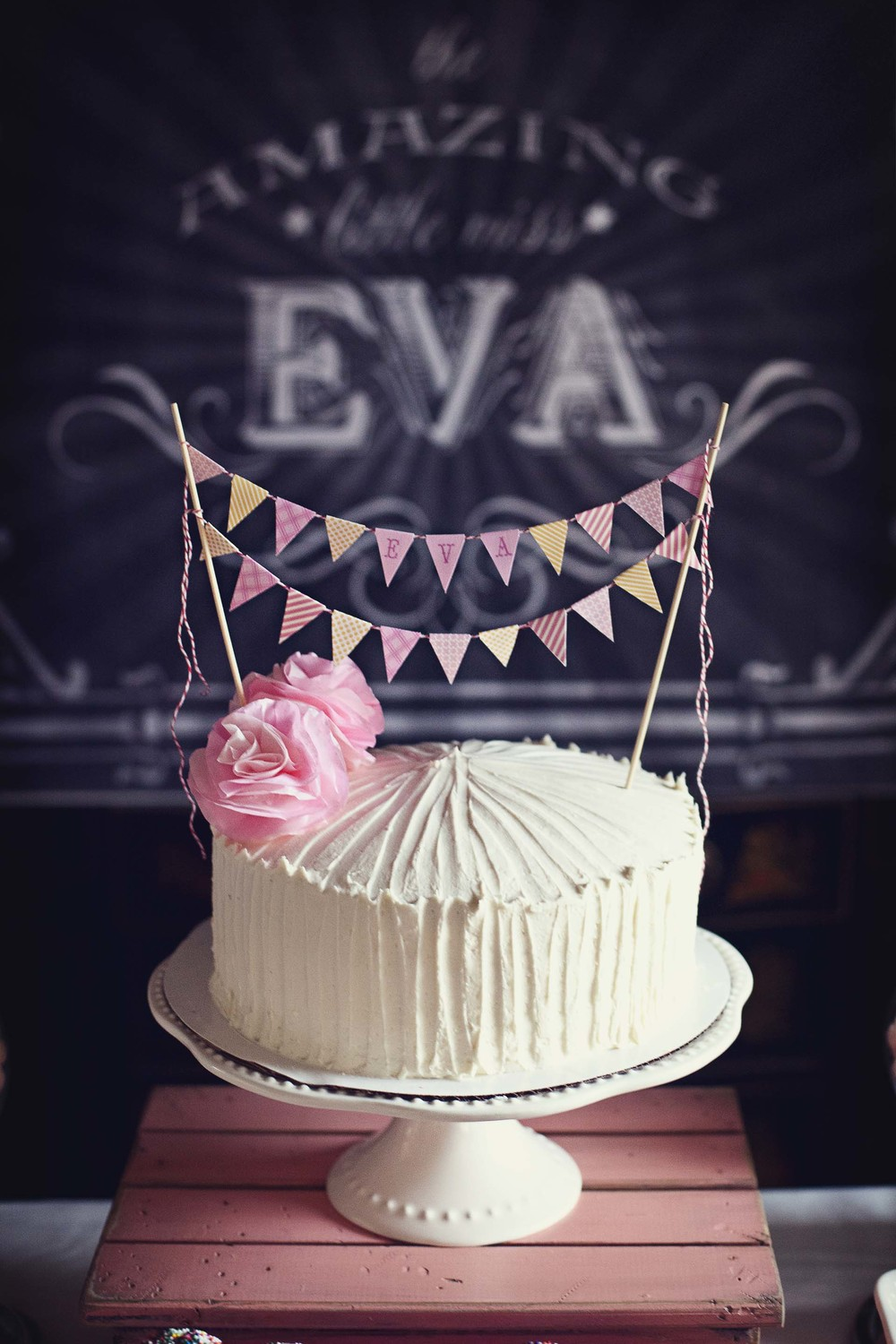 "To compliment  our yellow and pink color scheme, we chose a strawberry lemonade buttercream cake and embellished it with tissue paper flowers and handmade bunting.   I designed the vintage poster you see in the background and had it printed at Staples as an engineer print (less than $7 for a 36""x48"" print)."