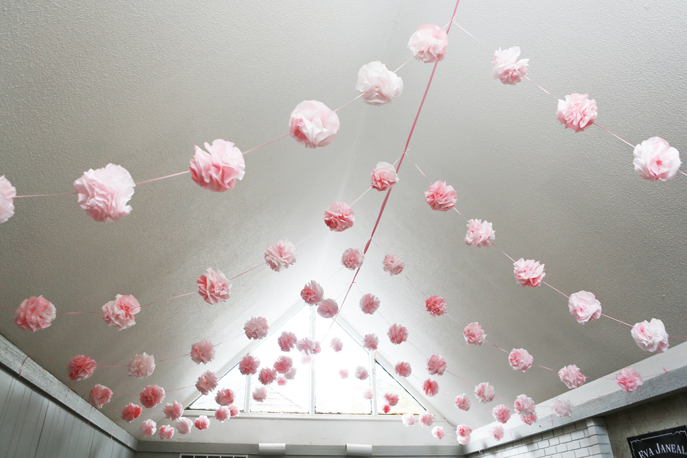 "Our vaulted ceiling was perfect for a ""big-top"", so I made pom-poms out of kool-aid stained coffee filters and spare ribbon. Total cost for 1000 coffee filters and 2 packs of kool-aid , $5."