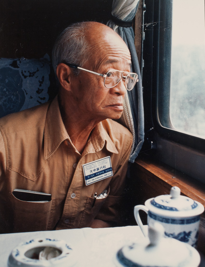 Dick Keong Wong looks out a train window at the Chinese countryside.