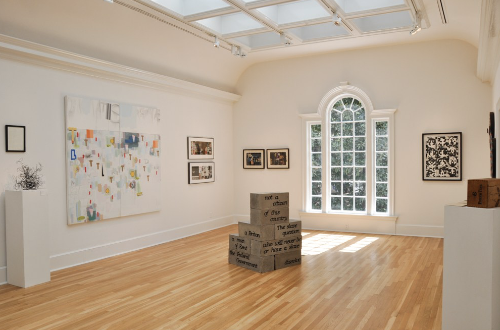 "Installation view of ""Beyond Words"" at Swan Coach House Gallery, with a painting by Craig Drennen on left wall, sculptures by Mary Stuart Hall on floor, and a work by Esteban Patino on back right wall."