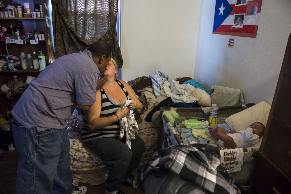Syracuse resident and former addict Jose Moralles, 47, leans in to kiss his wife Frances before heading out to the area around the Rescue Mission to sell cigarettes. In addition to the family receiving food stamps, Jose sells both single and packs of Lucy's cigarettes on the streets of Syracuse to support his wife, and his four-month-old son Jose Jr.