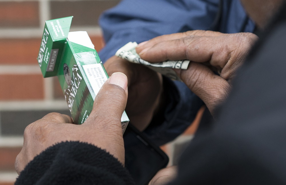 Syracuse resident and former addict Jose Moralles, 47, makes an exchange of a pack of Lucy's cigarettes for cash on a street that runs parallel to the Rescue Mission. Moralles sells packs of Lucy's for five dollars each, and single cigarettes for 25 cents a piece.