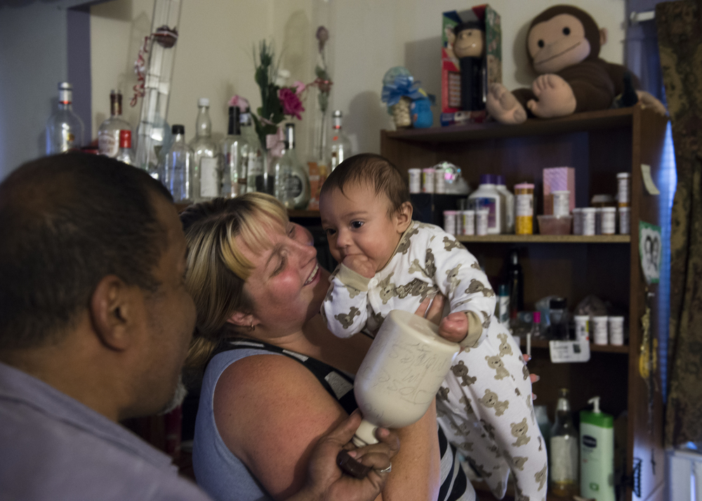 Syracuse resident and former addict Jose Moralles, 47, shakes a bottle full of change to amuse his four-month-old son, Jose Jr. Moralles has been saving change in the bottle his son, but occasionally dips into his funds to purchase alcohol for himself.