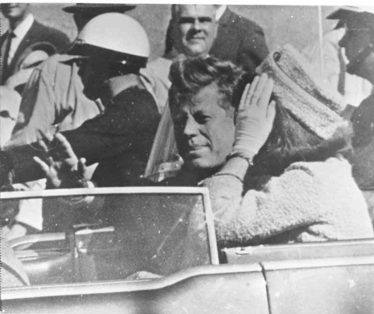 Photo 31- President Kennedy waves to the crowd moments before the shots are fired.png