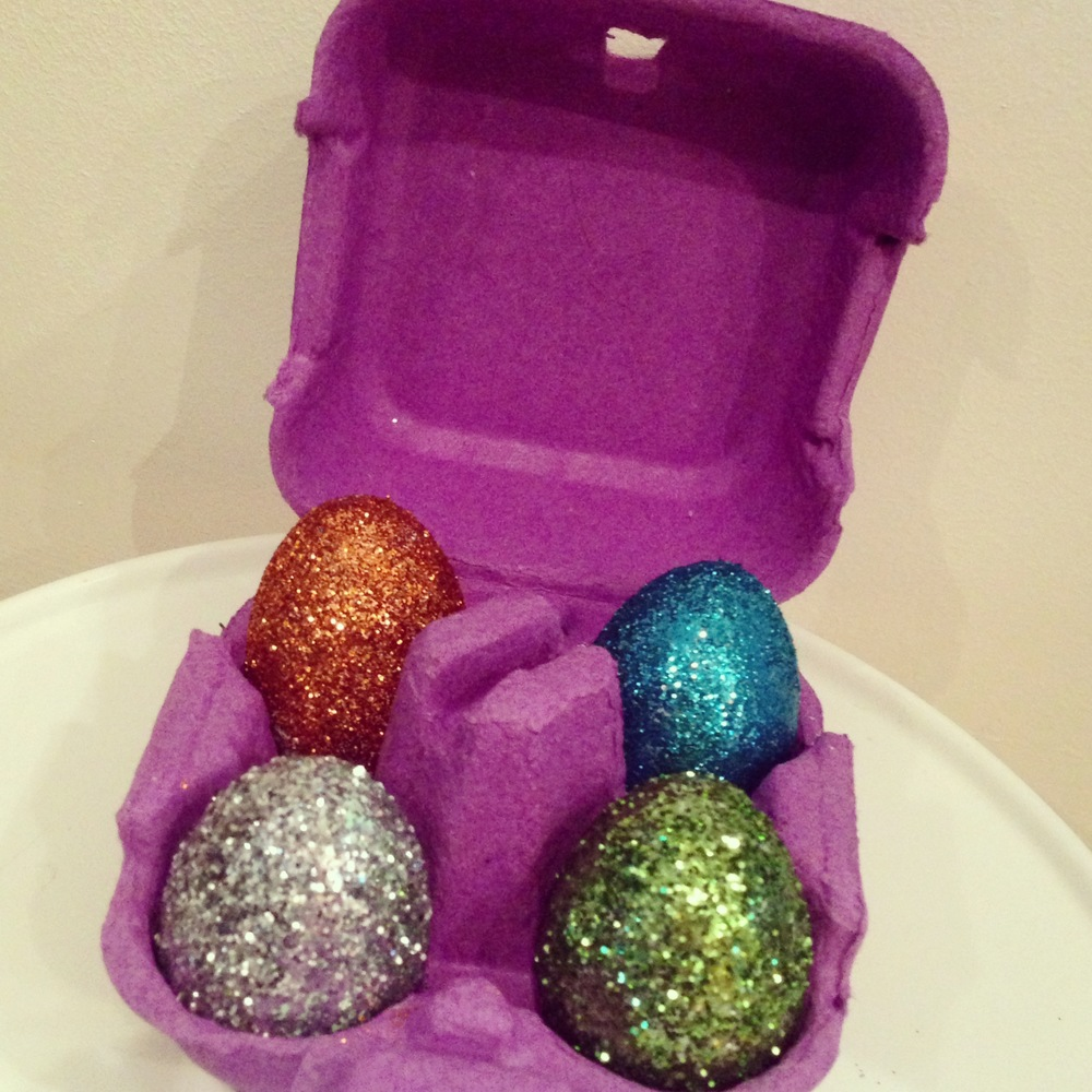 I bought some fake eggs this year and wanted to decorate them for my blog - I decided to go with glitter! This project is super easy for any age and is fast to do, the only downside is it can be rather messy! All you need is PVC glue, a glue brush, a range of glitters and ensure you have some newspaper to protect the area you're working on. I saved this coloured egg box from some yummy Cadburys 'Egg 'n' Spoon eggs but any will do from your regular eggs at home.   + Apply the glue with the brush (even spray glue could work - probably less sticky)  + Choose your glitter and sprinkle away - I used a scrap bit of paper to place underneath when sprinkling so I could gather the excess glitter so none was wasted  + Place in the box to dry and after 30mins or so give the eggs a shake to remove any excess glitter and they are ready to use as decoration.