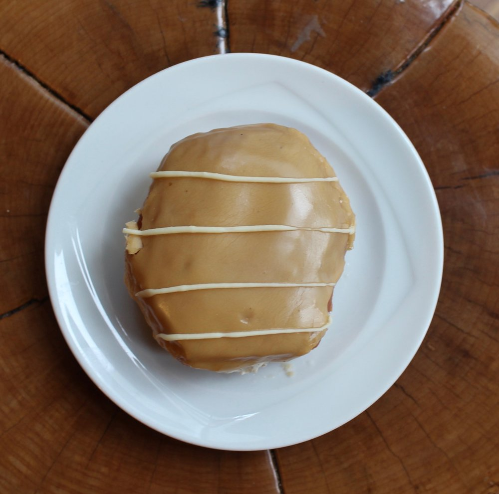 London Fog | Whipped cream infused with fresh ground organic London Fog tea and stuffed inside a yeasted donut. Glazed with earl grey glaze and topped with stripes of white chocolate ganache.