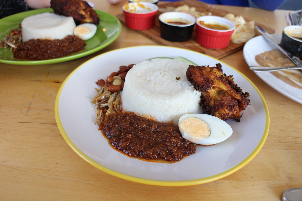 Nasi Lemak - A Malaysian breakfast staple of fried spiced chicken, sambal, crispy anchovies. peanuts, slices of cucumber and boiled egg served with fragrant coconut rice $11.50