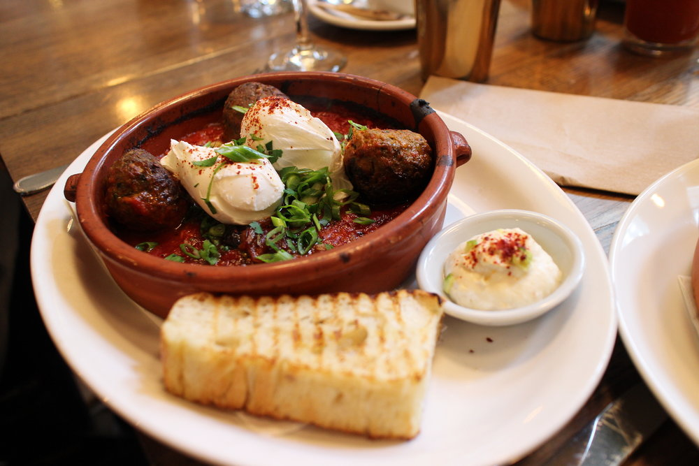 Les Boulettes | Poached eggs, spicy Moroccan lamb meatballs, roasted pepper, black olive and tomato stew, raita, grilled focaccia