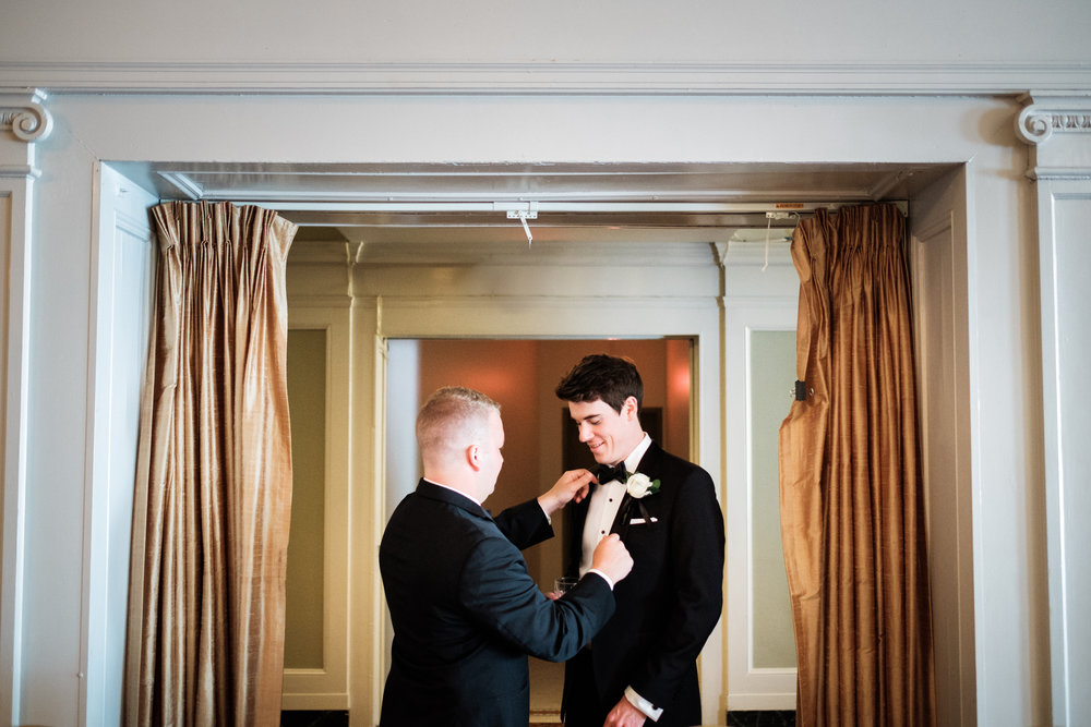 Best man helping the groom get ready for his duluth wedding