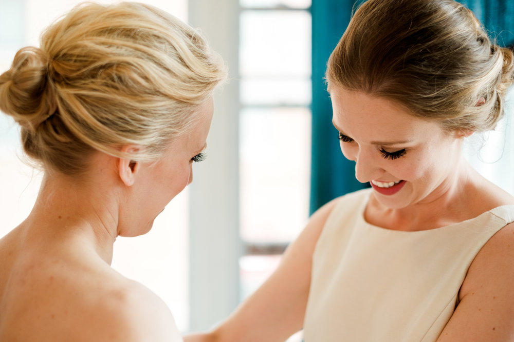 maid of honor fixing brides dress