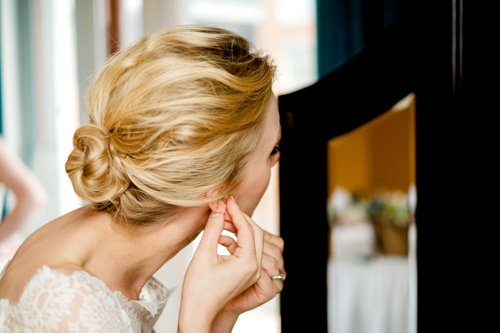 bride putting in her earring at greysolon ballroom