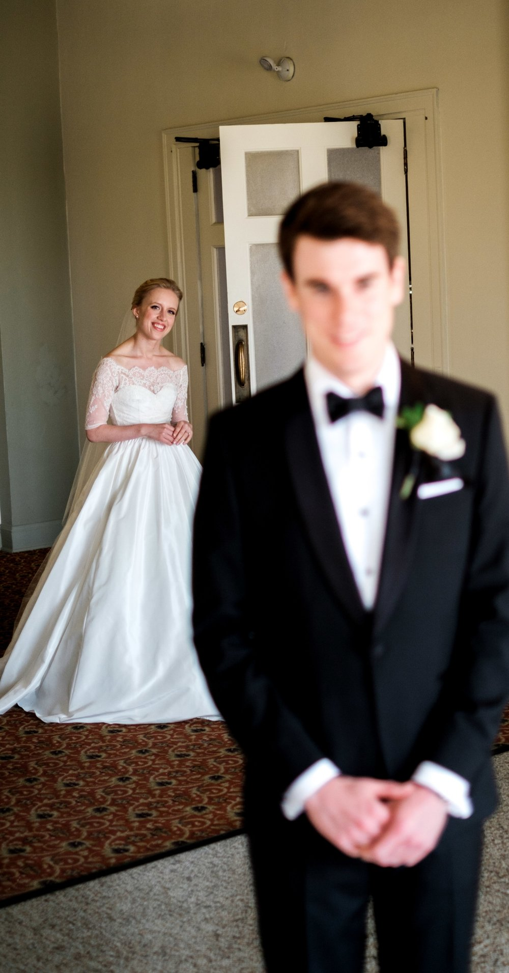 bride walking up behind her groom for their first look at greysolon ballroom