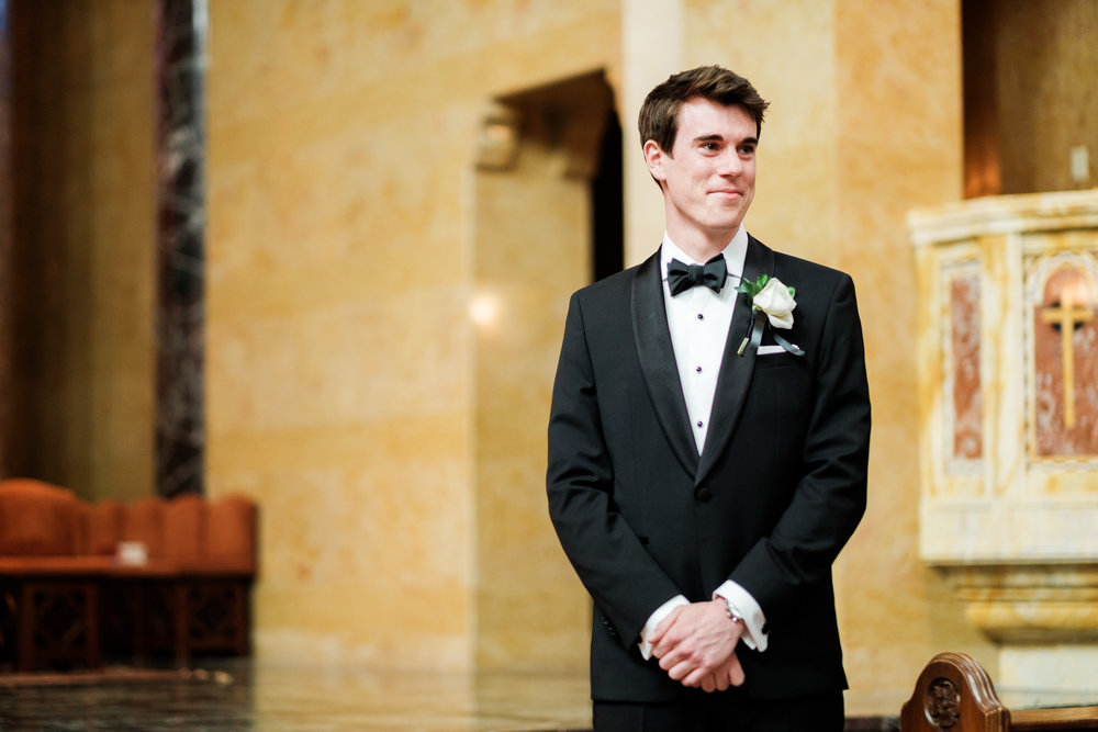groom waiting for his bride to walk down the aisle at duluth cathedral