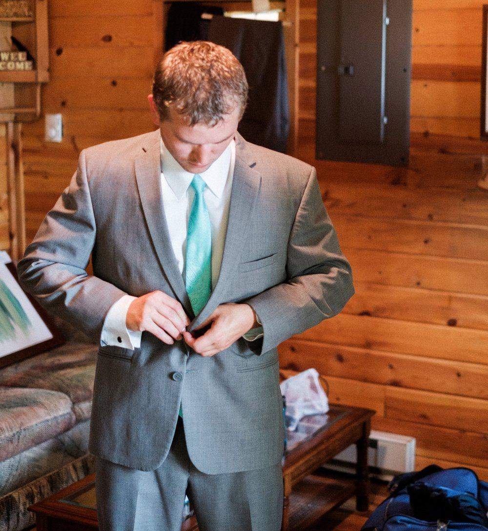groom putting on jacket on wedding day
