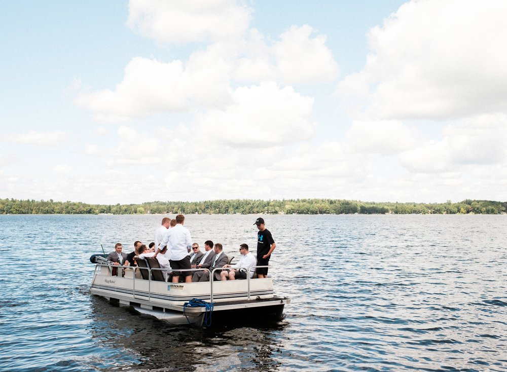 groomsmen taking a pontoon ride