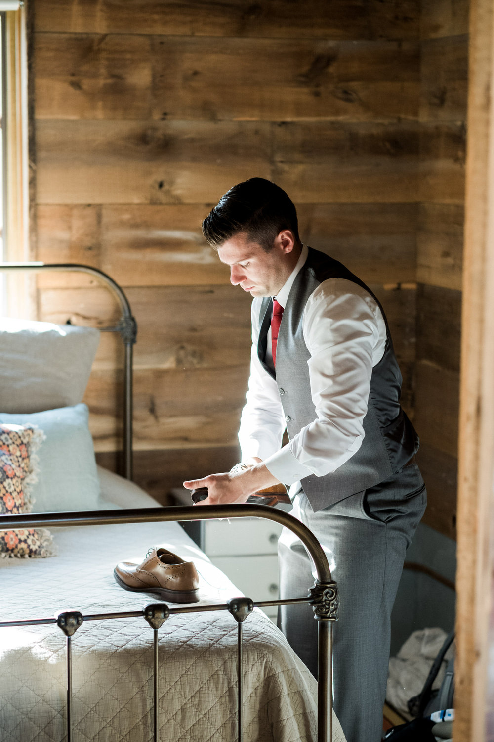 groom buffing shoes on wedding day