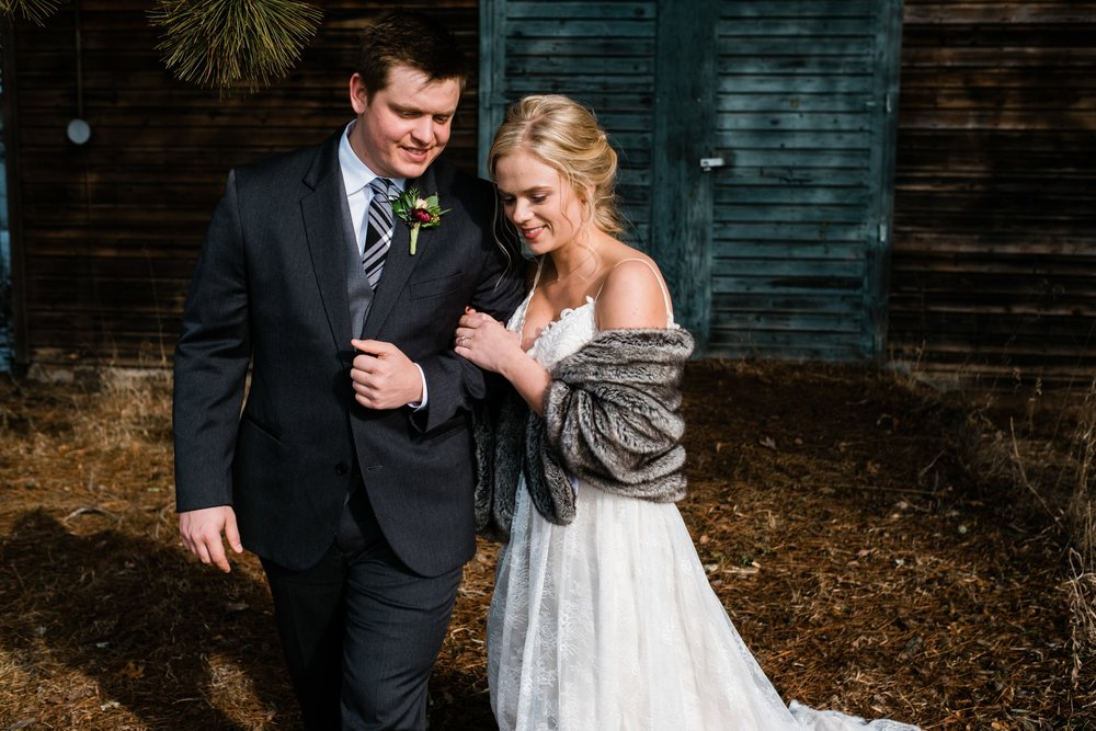 bride and groom walking on their winter wedding at a barn