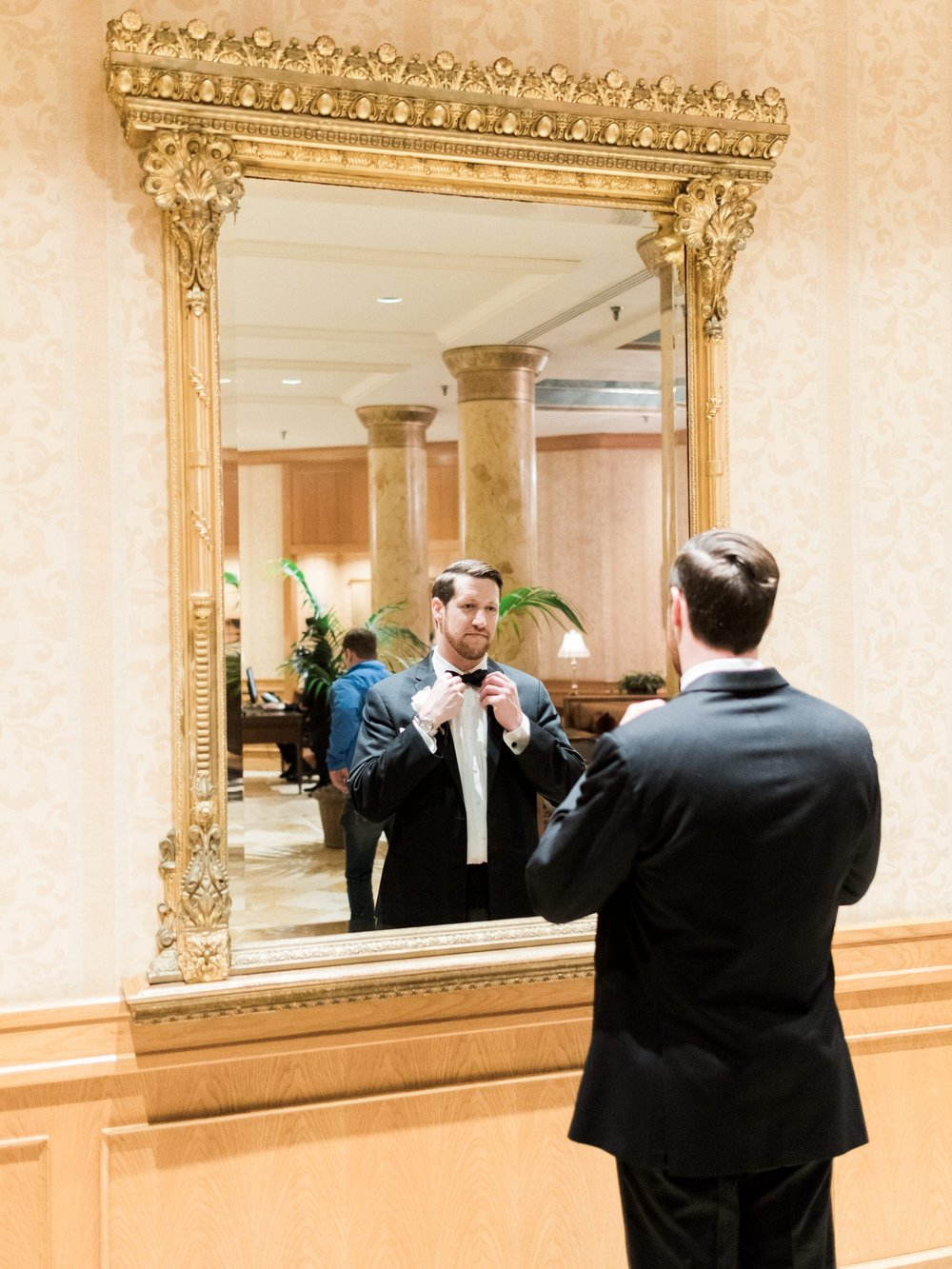 groom getting ready in the lobby of the Saint Paul Hotel