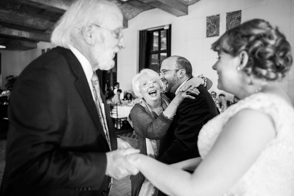 Family embracing bride and groom at San Francisco City Club