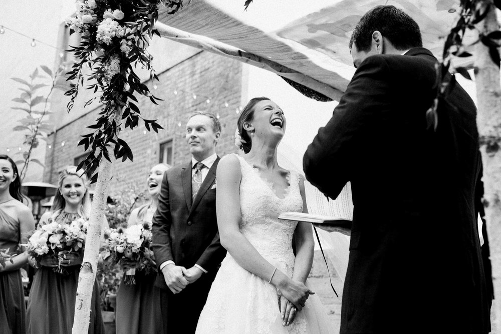Bride laughing at Jewish wedding ceremony under chuppah