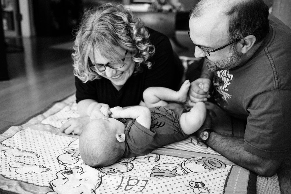Mother and father playing with baby on blanket
