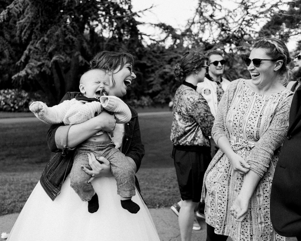 Bride holding baby and laughing with friends