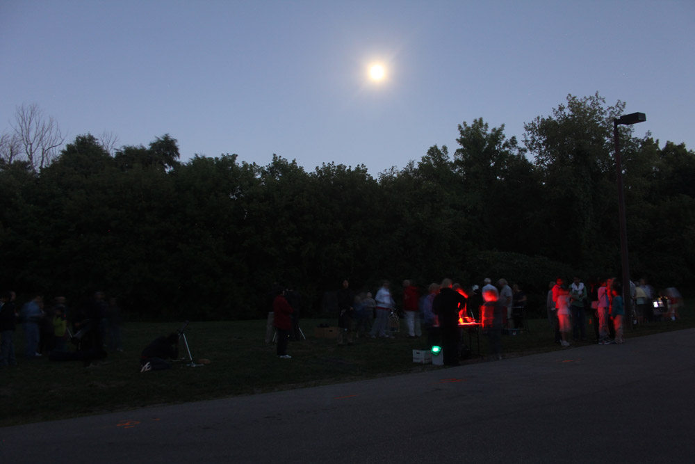 Telescopes at a Riverwood star party are illuminated by red lights as visitors observe the Moon.