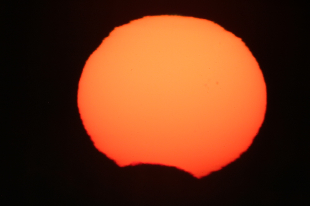 "The Moon takes a small bite out of the Sun Sunday morning at sunrise as seen from Jack Darling Park in Mississauga. Photo by Randy Attwood using a Questar 3.5"" telescope with solar filter, Canon Camera."
