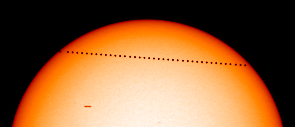 A transit of Mercury - the planet can be seen slowly moving across the face of the Sun.
