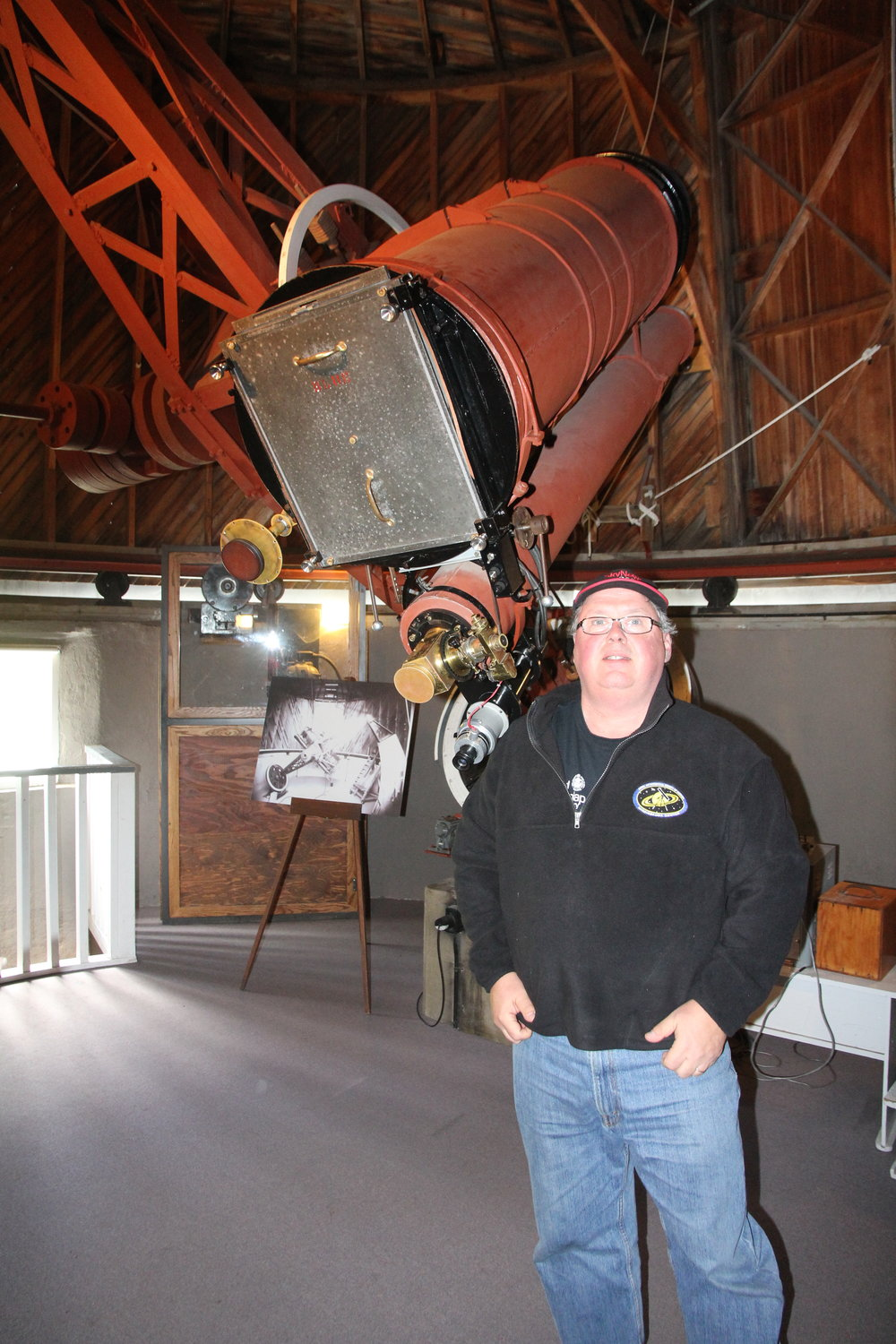 Randy Attwood stands in front of the telescope/camera used to discover Pluto in 1930.