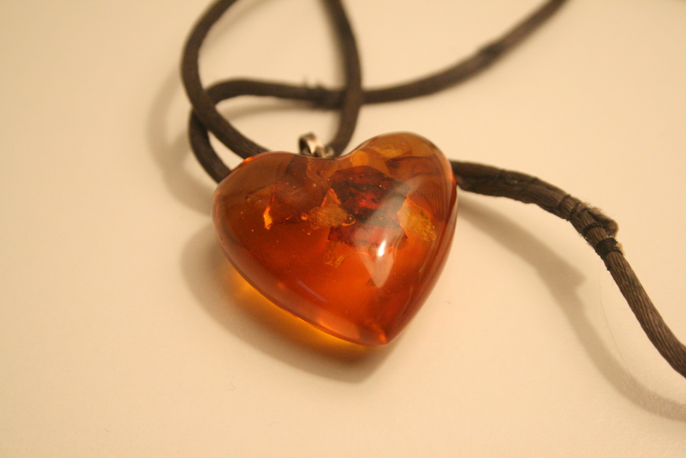 Object: Amber Heart This necklace was given to me for my 8th Christmas from my neighbors and surrogate grandparents Barbara and Harry Double. I wore this amber heart almost every day of 4th grade. The silk chord was sewn together as a makeshift chain by Harry Double who is now 94 years old. Barbara passed away in 2010 and is missed everyday by those who knew her.  Location: Berkeley, California Submitted by: Allyson Feeney