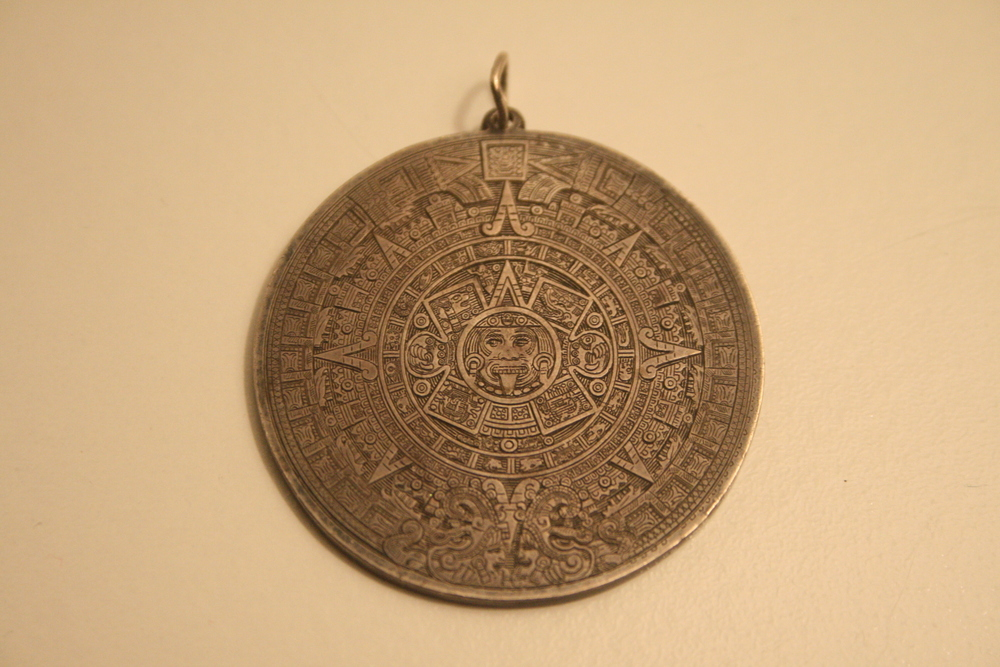 "Object: Medallion In the 1890s my great great grandfather Max Loeb moved to Mexico City to begin a china import and export business. He and his wife Florence Rubel Loeb built a house on Calle Liverpool in what clearly was the European section of Mexico City. In 1911 the family had to flee the city because of the Mexican Revolution. This medallion is marked with Max Loeb's initials on one side and a beautifully intrique Aztec calendar on the other. My grandmother ""Happy"" Harriet Loeb Feeney passed this medallion down to me along with a number of family heirlooms from this period of time. I scrubbed the tarnish away to reveal this delicate turn of the century metalwork."