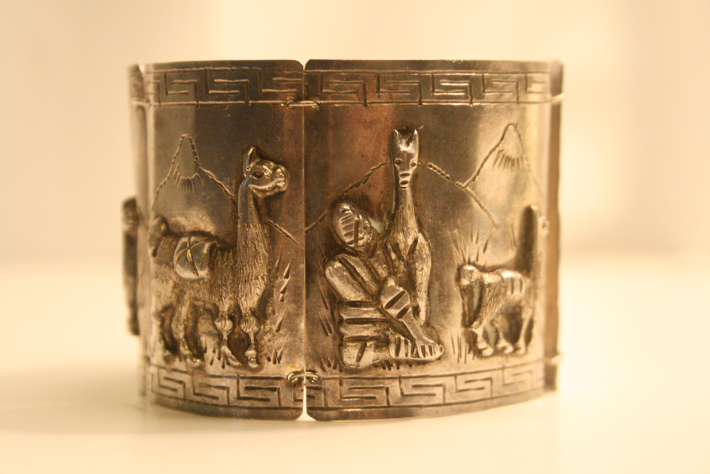 "Object: Llama bracelet My grandmother ""Happy"" Harriet Loeb Feeney gave me this silver cuff bracelet around 2007. She has always travelled extensively and collected treasures along the way. I would be guessing on the date but it was clearly purchased for her in Peru. Judging by the tarnish and craftsmanship of the item, I would guess it came from the first half of the 20th century. It is a 5 panel raised and carved narrative of a shepherd and his llamas trekking across the Andes. Every time I wear it I feel connected to her and her world travels."