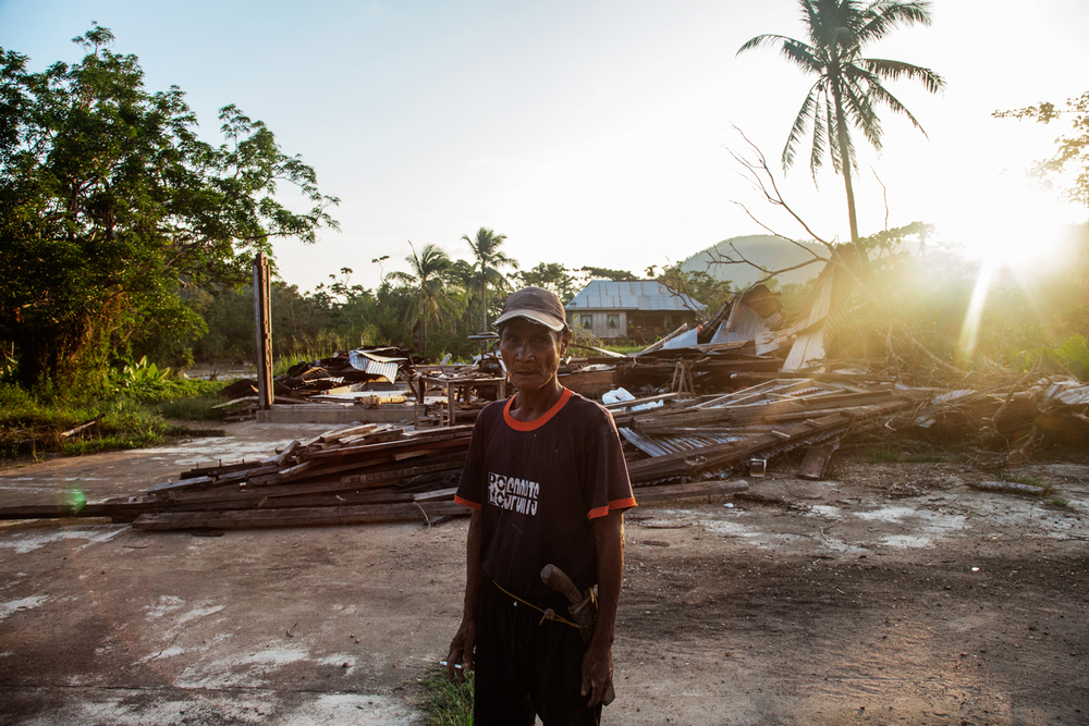 An indigenous migrant from Culion living on Busuanga Island in Northern Palawan stands in front of a building leveled by Typhoon Haiyan in 2013.