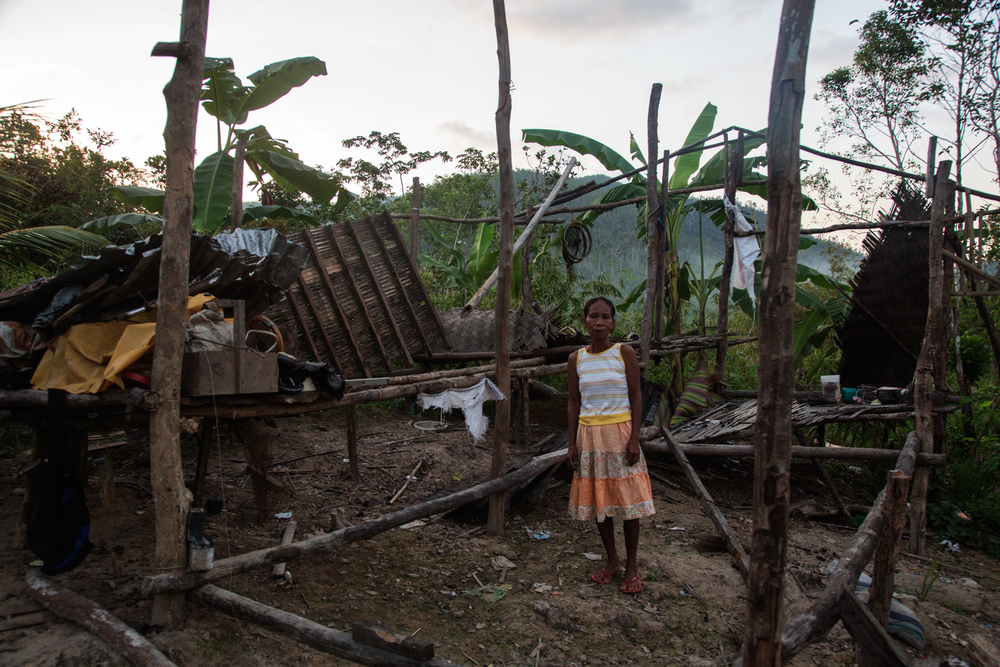 A migrant from Culio living on Busuanga Island in Northern Palawan stands in front of her house that was destroyed by Typhoon Haiyan.