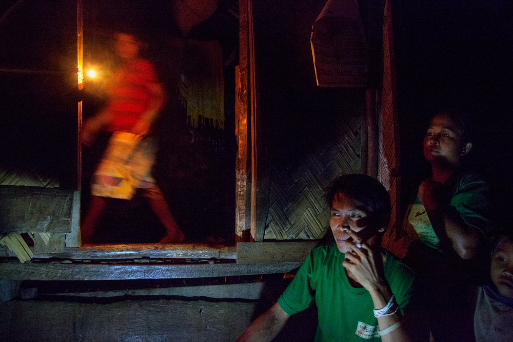 A family in the Tula-Tula community sit together in the light of a battery powered lamp and oil lamp outside their family home. In 2011 they were fighting against mining explorations in the area. Currently their area is safe but the issue of mining remains a major threat to their homelands.