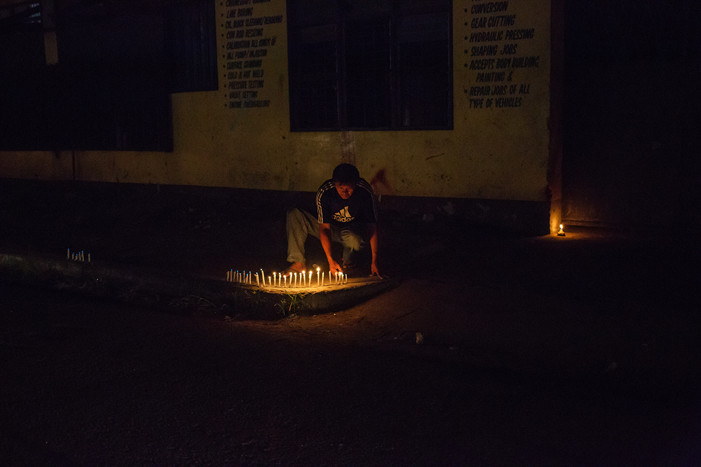 A man lights candles for loved ones lost on the one year anniversary of the landfall of Typhoon Haiyan in Tacloban, Leyte, the Philippines.