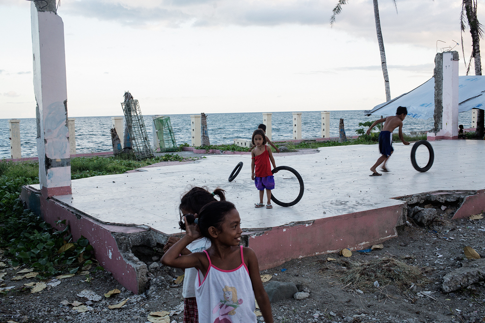 Children play in the ruins of a building in the tent village near San Jose airport, Tacloban City, Leyte in the Philippines on November 8, 2014 one year after the destruction of the landfall of Typhoon Haiyan.