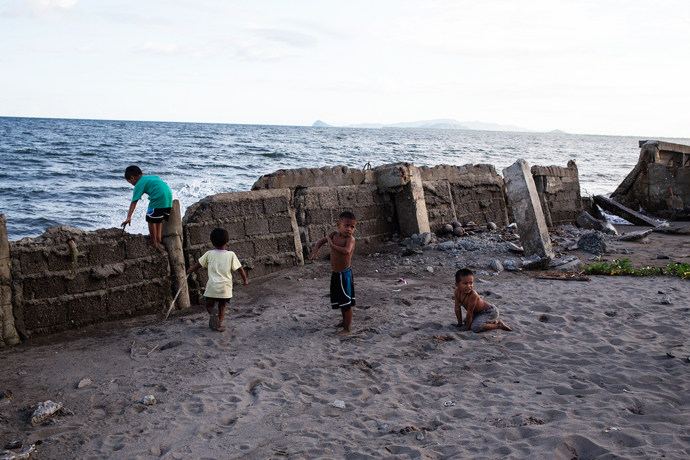 Children play by the water, on a wall torn apart by Typhoon Haiyan in the tent city near San Jose airport, Tacloban Leyte.