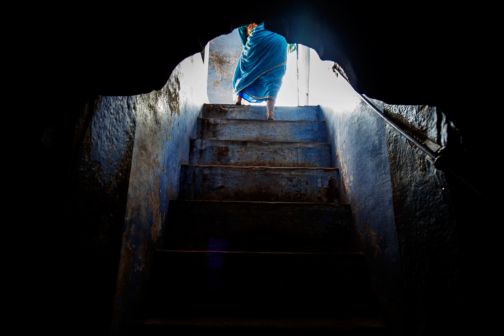 A woman walks upstairs to a communal area from her sleeping quarter in the ashram.