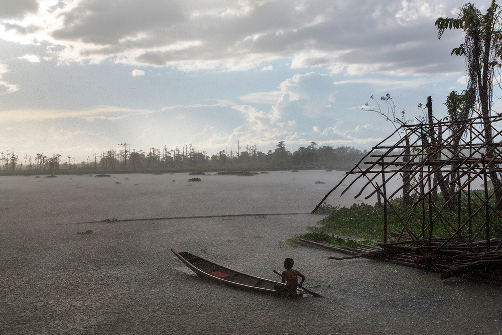 A young Monobo boy guides his canoe through an unexpected rainfall in a community floating village in the middle of Agusan Marsh, Mindanao in the Philippines.