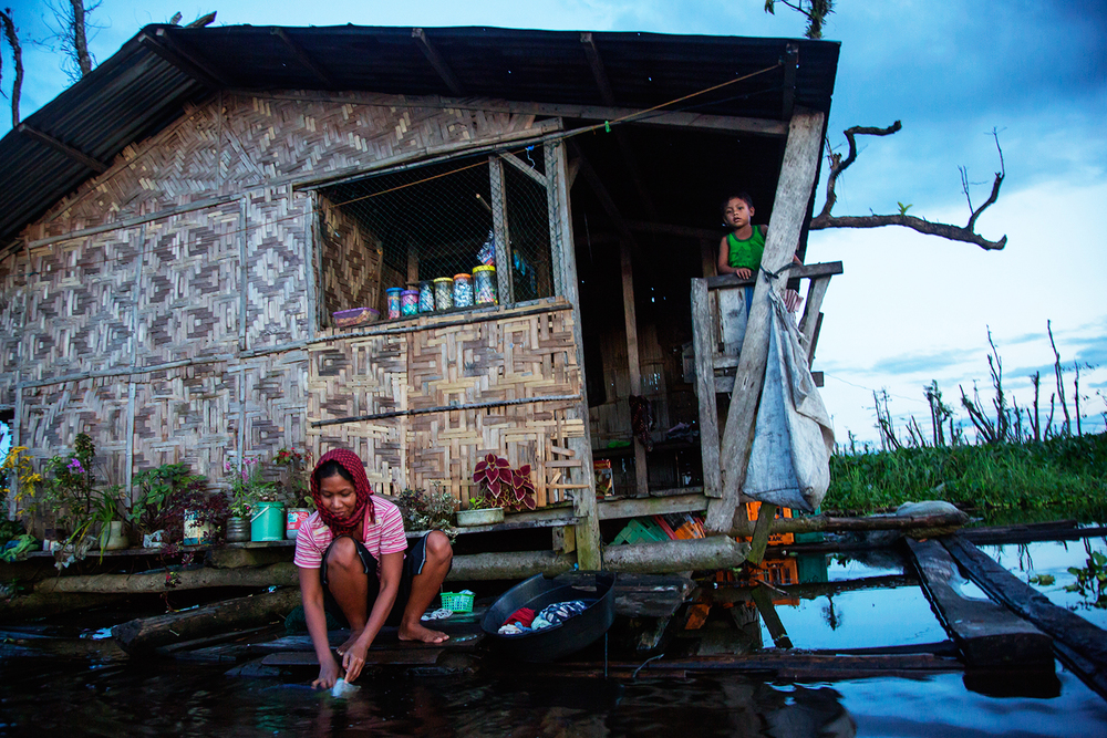 A woman from the Monobo community of Agusan Marsh washes the family dishes outside her home at sunset in the floating village.