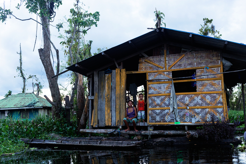 A woman and child sit on the front step of their floating home in the floating village in Agusan Marsh in Mindanao, the Philippines.