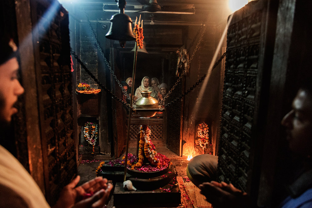Widowed women and young Brahmin priests perform evening Aarti in the ashram temple overlooking the Ganga River in Varanasi, Uttar Pradesh India.
