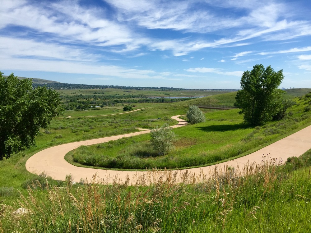 The trail winds up and out of Bear Creek Lake Park before connecting to the C-470 trail. The view takes in Bear Creek Lake Park and Green Mountain in the distance